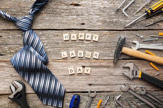 Feliz dia do trabalho em blocos de madeira com ferramentas de construção e uma gravata na vista superior do plano de fundo de madeira