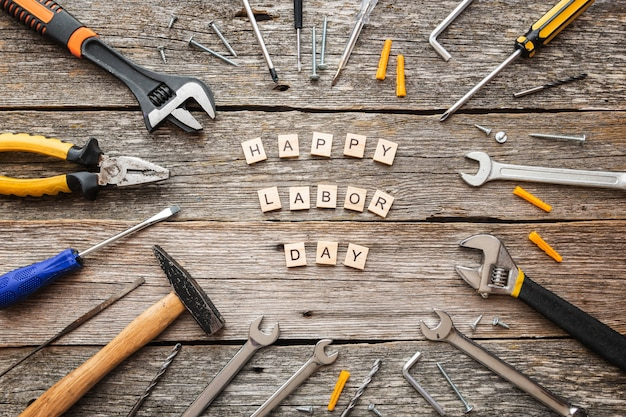 Feliz dia do trabalho em blocos de madeira e ferramentas de construção na vista superior do plano de fundo de madeira