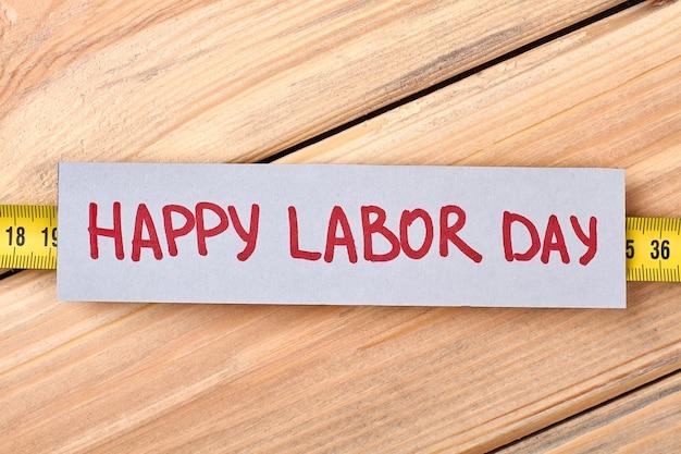Feliz dia do trabalho papel de saudação. fita métrica em fundo de madeira. cartão de felicitações feito à mão.