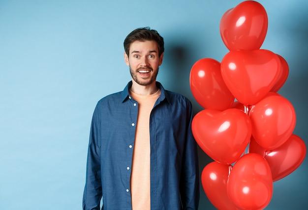 Feliz dia dos namorados. cara sorridente animado em pé perto de balões de corações vermelhos e olhando para a câmera, fundo azul.