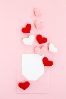 Feliz dia dos namorados cartão com corações rosa, brancos e vermelhos espalhando sobre fundo rosa. mensagem de amor.