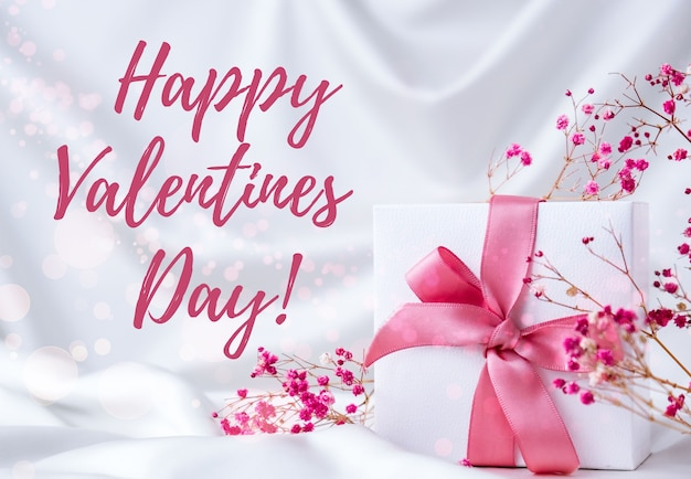Feliz dia dos namorados cartão letras de saudação. caixa de presente com flores rosa secas de fita rosa. conceito de pastel de luz brilhante.