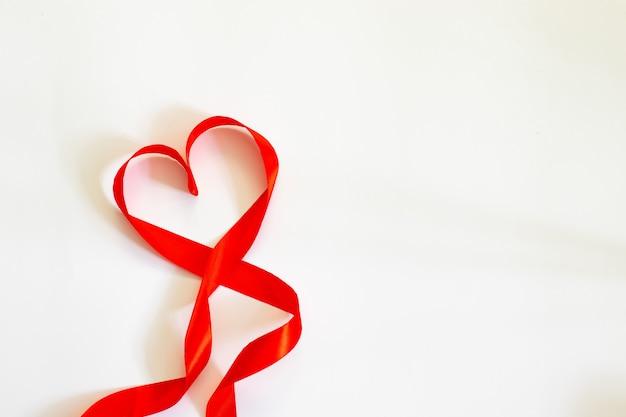Feliz dia dos namorados. coração vermelho da fita no fundo branco.