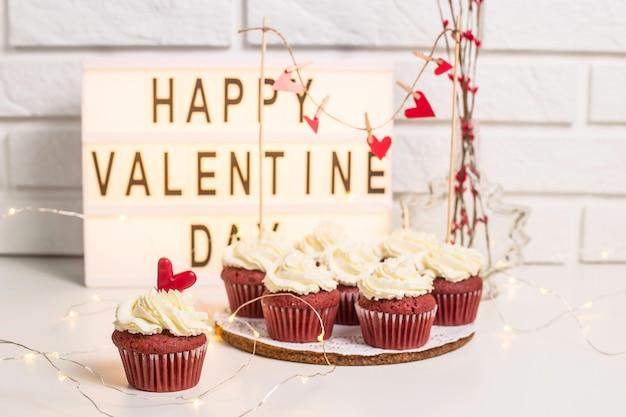 Feliz dia dos namorados está escrito em uma lâmpada decorativa ao lado de cupcakes vermelhos