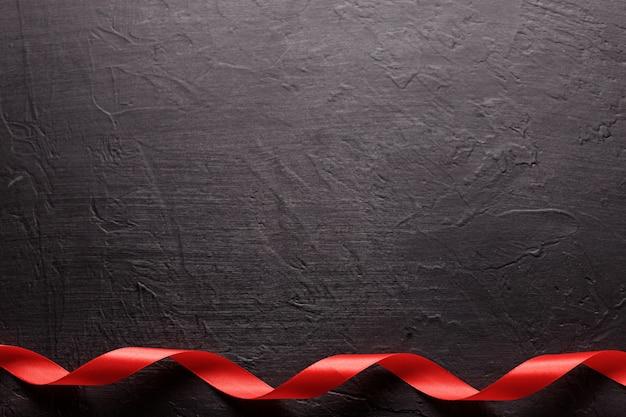 Feliz dia dos namorados. fita vermelha em fundo de pedra preta. conceito de dia dos namorados