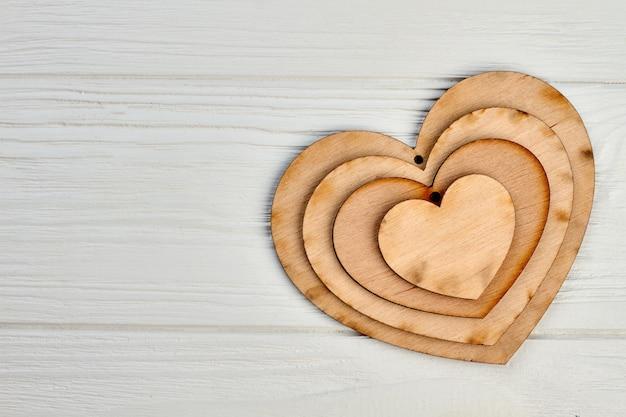 Feliz dia dos namorados fundo de madeira. coleção de corações de madeira compensada e espaço de cópia. cartão do feriado do dia dos namorados.