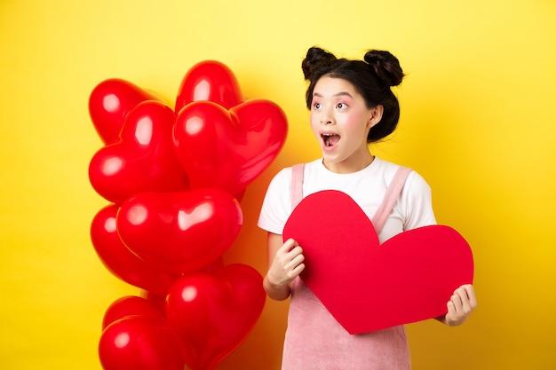 Feliz dia dos namorados. menina asiática animada e surpresa conferindo uma oferta romântica