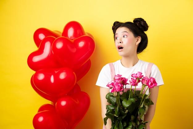Feliz dia dos namorados. menina asiática surpresa olhando para a esquerda com cara de boba