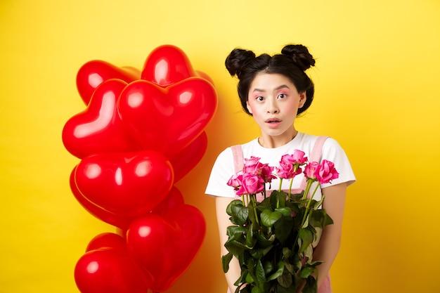 Feliz dia dos namorados. menina asiática surpresa recebe buquê de rosas cor de rosa do amante, olhando com admiração para a câmera, em pé perto de balões de coração vermelho, fundo amarelo.