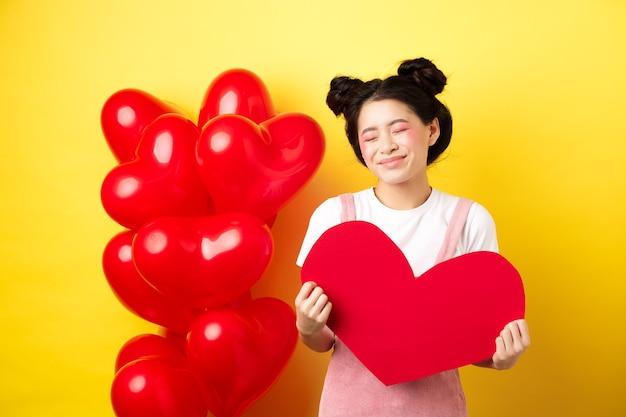 Feliz dia dos namorados. mulher asiática boba e bonita sorrindo sonhadora, mostrando o coração vermelho, imaginando o encontro romântico com o amante, de pé sobre fundo amarelo.