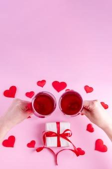 Feliz dia dos namorados saudações. as mãos seguram duas taças de vinho sobre um presente em papel de embrulho branco com uma fita vermelha em um fundo rosa decorado com formas de coração vermelho, vista superior, moldura vertical.