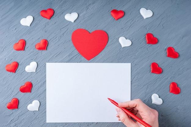 Feliz dia dos namorados saudações. mão segura uma caneta vermelha para escrever uma carta de amor ou parabéns sobre um fundo cinza