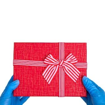 Feliz dia dos namorados saudações. mãos em luvas médicas azuis seguram uma caixa de presente vermelha com fita isolada na mesa branca, quadrado, espaço de cópia.