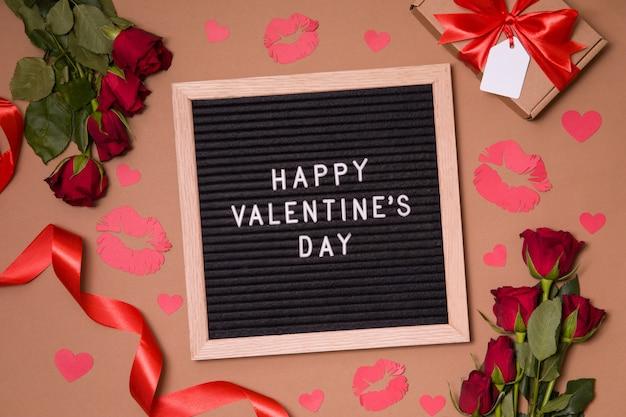 Feliz dia dos namorados - texto na placa da letra com fundo de dia dos namorados - rosas vermelhas, beijos e corações.
