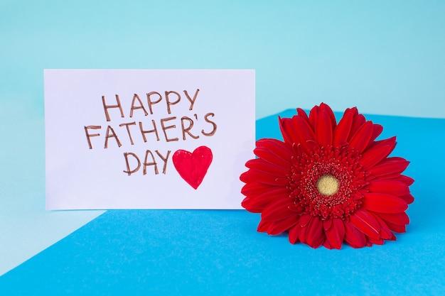 Feliz dia dos pais. cartão com a inscrição feliz dia dos pais e flor gerbera vermelha