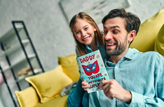 Feliz dia dos pais! filha parabenizando o pai e dando-lhe o cartão postal. papai e menina sorrindo e se abraçando. férias em família e união.