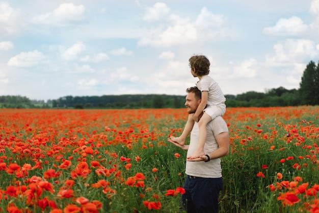 Feliz dia dos pais, filho e pai brincando em um lindo campo de papoulas vermelhas