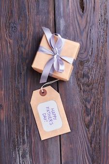 Feliz dia dos pais saudação tag. presente com laço em madeira. boa decisão para marcar presentes.