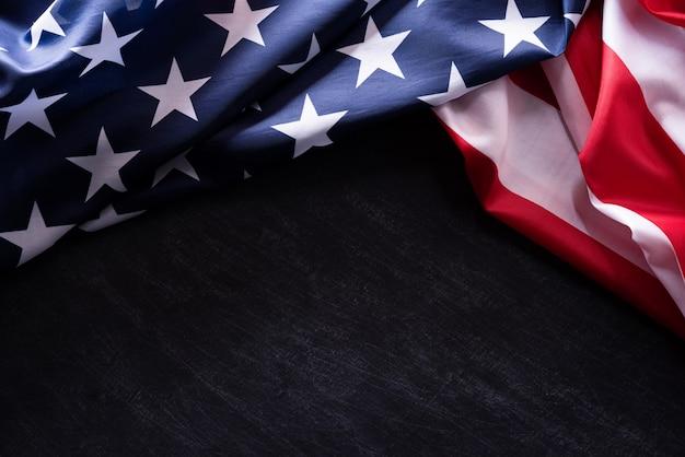 Feliz dia dos veteranos. veteranos das bandeiras americanas contra um fundo do quadro-negro.