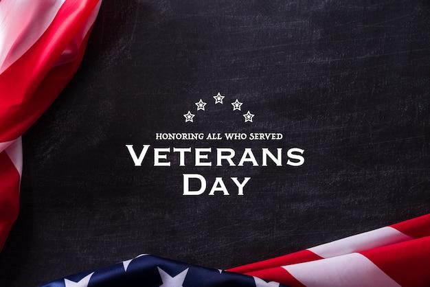 Feliz dia dos veteranos. veteranos das bandeiras americanas contra um quadro-negro.