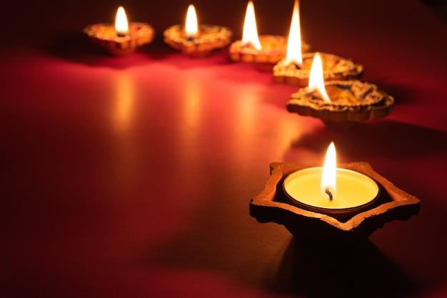 Feliz diwali - clay diya lâmpadas acesas durante dipavali, festival hindu de celebração de luzes.