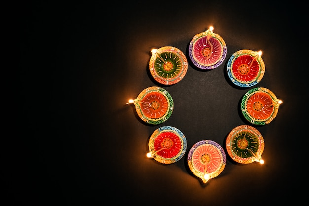 Feliz diwali - festival hindu, diya de lâmpada de óleo tradicional colorido sobre preto