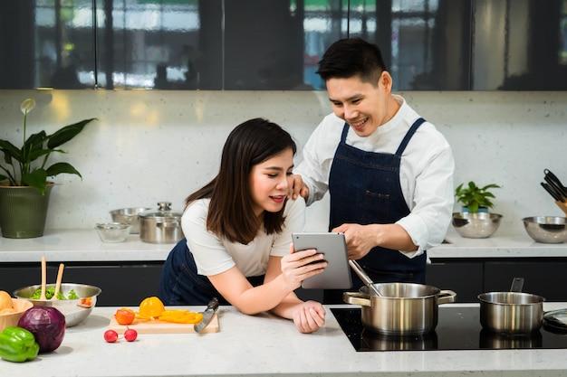 Feliz do chef casais asiáticos cozinhando na cozinha.