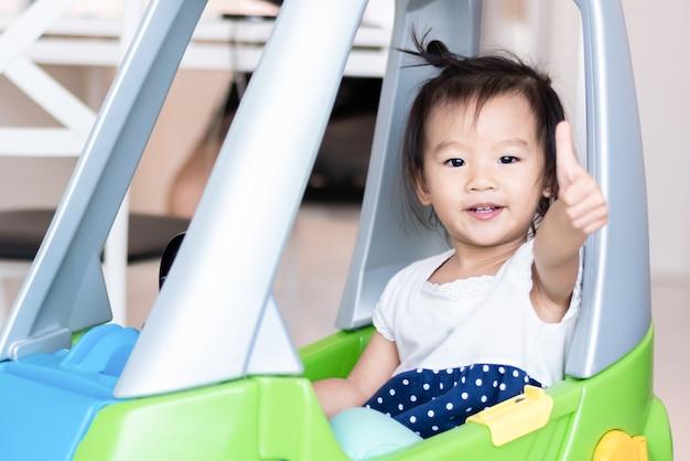 Feliz doce menina asiática pequena andar de carro pequeno com o polegar para cima isolado no branco