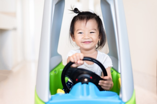 Feliz, doce, pequeno, menina asiática, montando, ligado, carro pequeno, com, sorrindo