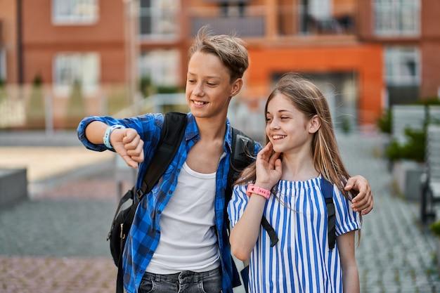 Feliz dois alunos amigos menino e menina usando relógio inteligente, perto da escola.