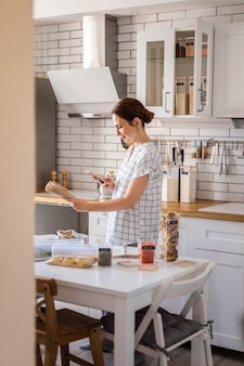 Feliz dona de casa sorrindo posando e tira fotos do código de barras na cozinha moderna de estilo nórdico.