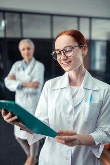 Feliz doutor. sorridente, jovem e bonita médica olhando para uma prancheta em pé no corredor ao lado de seu colega sênior