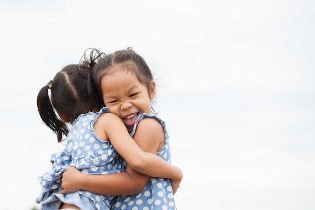 Feliz duas meninas asiáticas abraçando-se com amor