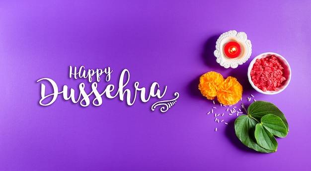 Feliz dussehra. flores amarelas, folhas verdes e arroz em fundo roxo pastel