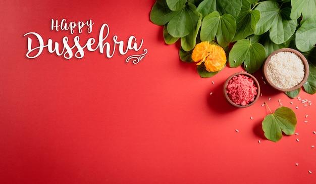 Feliz dussehra flores amarelas folhas verdes e arroz em fundo vermelho
