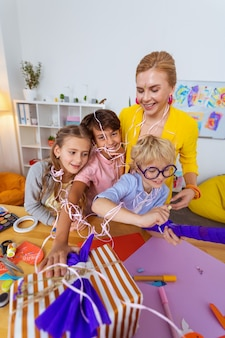 Feliz e alegre. alunos engraçados se sentindo felizes e alegres após uma incrível aula de arte com o professor
