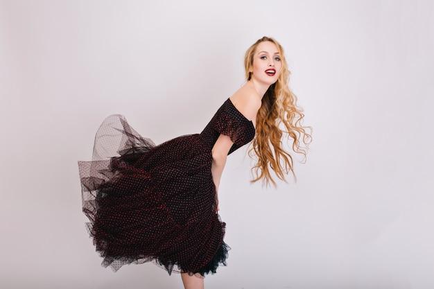 Feliz e alegria linda garota com cabelo longo cacheado loiro, modelo posando. usando maquiagem brilhante, vestido preto com saia fofa. comprimento total.