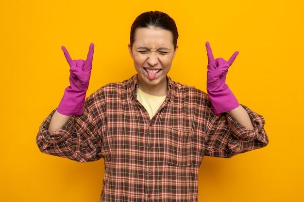 Feliz e animada jovem faxineira com roupas casuais e luvas de borracha, mostrando o símbolo do rock esticando a língua em pé na laranja