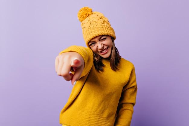 Feliz e animada piscadelas e sorrisos amigáveis. retrato de um blogueiro estiloso apontando para a frente