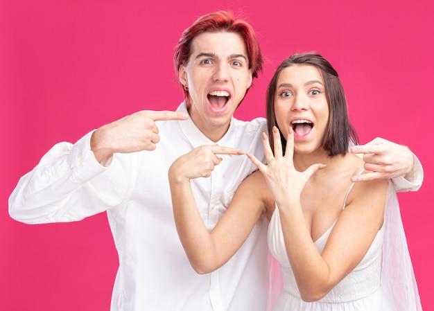 Feliz e animado casal de noivos, noivo e noiva se divertindo, posando juntos, apontando para a aliança de casamento no dedo, felizes apaixonados juntos