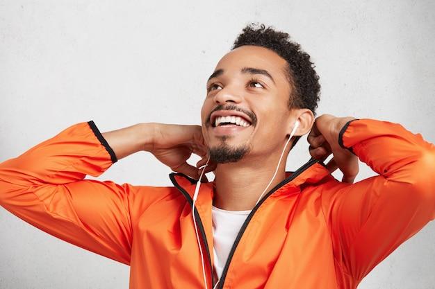 Feliz e animado jovem esportista usa jaqueta, olha para cima com um sorriso, ouve música como se fosse correr de longa distância.