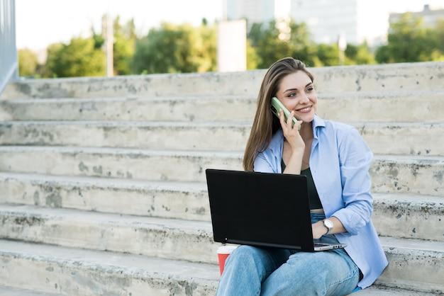 Feliz e atraente garota caucasiana está sentado com um laptop nas escadas e falando ao telefone. trabalho à distância. conceito freelance