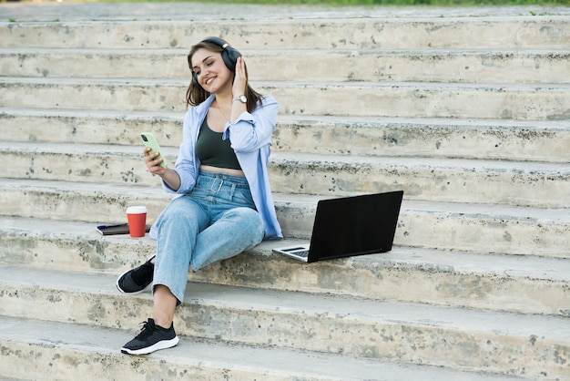 Feliz e atraente garota caucasiana sentada com um laptop nas escadas e segurando um telefone, ouvindo música em fones de ouvido