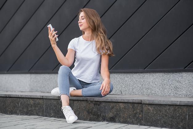 Feliz e atraente garota loira caucasiana está usando um smartphone.