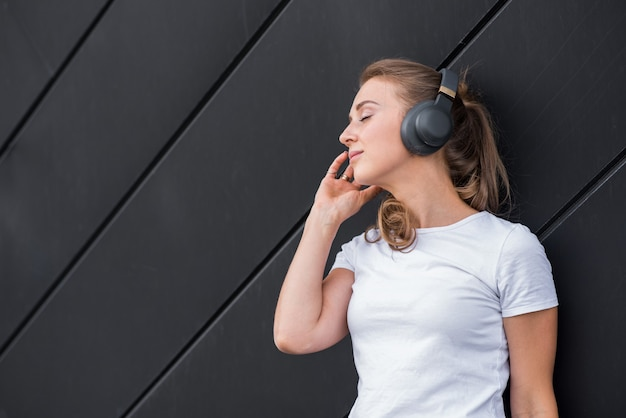Feliz e atraente garota loira caucasiana, ouvindo música com fones de ouvido e desfrutando sobre fundo preto.