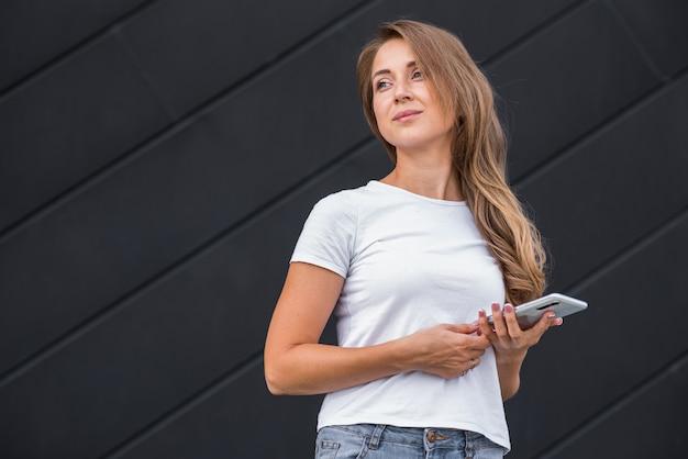 Feliz e atraente garota loira caucasiana usando um smartphone sobre fundo preto.