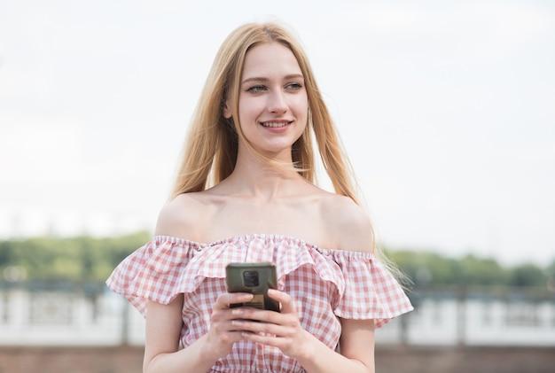 Feliz e atraente garota loira segurando um smartphone. trabalho online. freelance