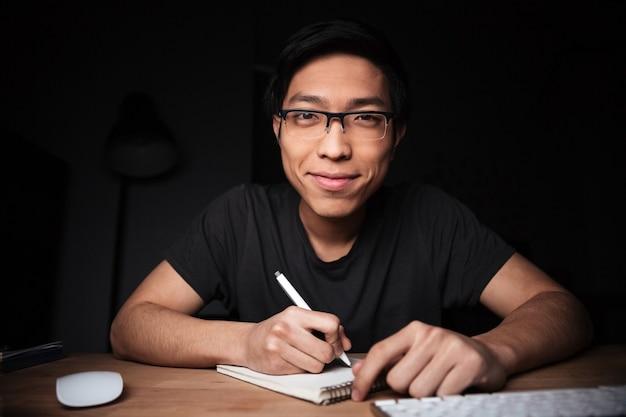 Feliz e atraente jovem asiático de óculos escrevendo e sorrindo em um quarto escuro.