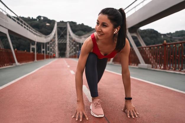 Feliz e atraente jovem fitness corredor feminino esticando as pernas antes de correr na ponte ao ar livre