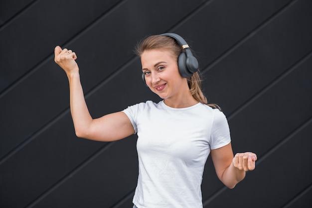 Feliz e atraente loira caucasiana, ouvindo música com fones de ouvido e dançando.